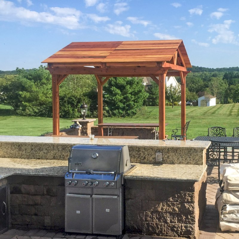 Del Norte Outdoor Kitchen Pavilion (Options: 12' L x 12' W, California Redwood, Unattached, 4-Post Kit for Concrete, Electrical Wiring Trim for 1 Post, 9' Posts, No Ceiling Fan Base, No Privacy Panels, No Curtain Rods, Transparent Premium Sealant). Photo Courtesy of Manjit Guleria of Pennington, NJ.