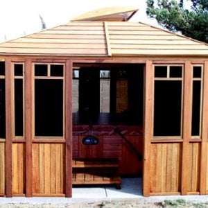 "DIY Wood Gazebo (14' L, 12' W, Mature Redwood, Sliding Windows, 4' x 6' Skylight, 24"" H Siding Below Windows, Vertical Siding, Japanese Doors, No Flooring, Transparent Premium Sealant). Photo also show a Spa Step inside the gazebo. Custom detail: Roof overhang was minimized per customer request."