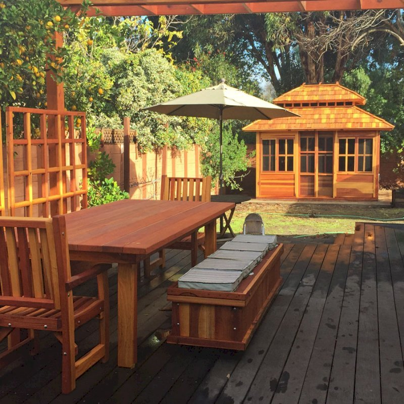 """Dream Gazebo (Options: 12' L, 10' W, California Redwood, All Sliding Windows with Screens, 4' x 4' Skylight, 30"""" H Siding Below Windows, Horizontal Siding, Japanese Doors, Complete Floor, Set of Shingles, Transparent Premium Sealant). Photo also shows a San Francisco Patio Table with 2 Ruth Chairs, a Storage Bench and Mendocino Planters with Trellises. Photo Courtesy of Tina Phi of Palo Alto, CA."""