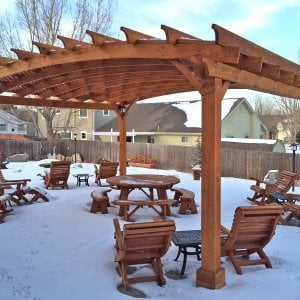 Ensenada Rocking Chairs (Options: Standard Width, Mature Redwood, No Cushion,Transparent Premium Sealant). Photo Also Shows an Arched Pergola, a Round Picnic Table Set, 4 Ensenada Easychairs with Ottomans and a Lutyens Bench in Background. Photo Courtesy of Mike Budzinak of Cheyenne, Wyoming.