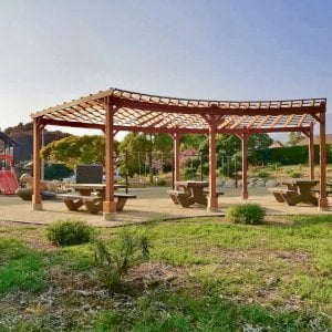 Fan Shaped Pergola Kit (Options: 22' x 25', California Redwood, With Roof Slats, No Electrical Wiring Trim Kit, 8-Post Anchoring for Concrete, No Ceiling Fan Base, 9.5' Posts, No Curtain Rods, Transparent Premium Sealant). Photo Courtesy of Vedic Education and Devotional Academy of Milpitas, California.