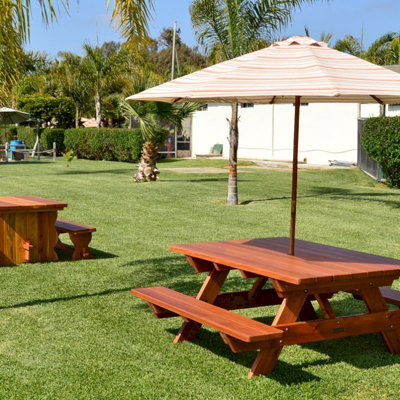 "Forever Picnic Table (Options: 6' L, 46"" W, Side Benches, Mature Redwood, Standard Tabletop, Rounded Corners, Umbrella Hole, Transparent Premium Sealant). Photo also shows a Trestle Table in background. Umbrella not included."