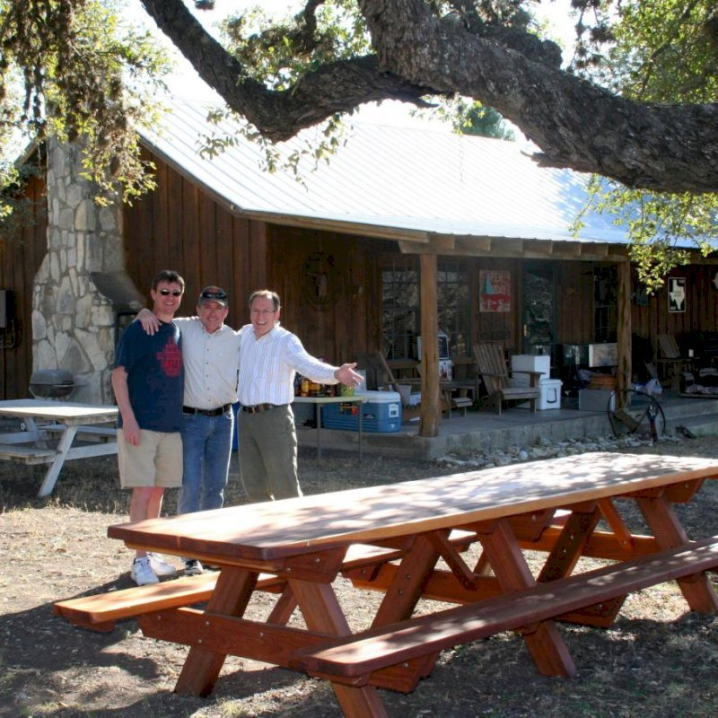 "Forever Picnic Table (Options: 12' L, 34 1/2"" W, Side Benches, Mature Redwood, Standard Tabletop, Slightly Rounded Corners, No Umbrella Hole, Transparent Premium Sealant). Photo Courtesy of Mr. Pat Ankney, W&M Ranch, Camp Wood, TX."