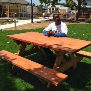 "Forever Picnic Table (Options: 6' L, 34 1/2"" W, Side Benches, Redwood, Standard Tabletop, SlightlyRounded Corners, No Umbrella Hole, Transparent Premium Sealant). Photo Courtesy of Pogo Park of Richmond, CA (www.pogopark.org)."