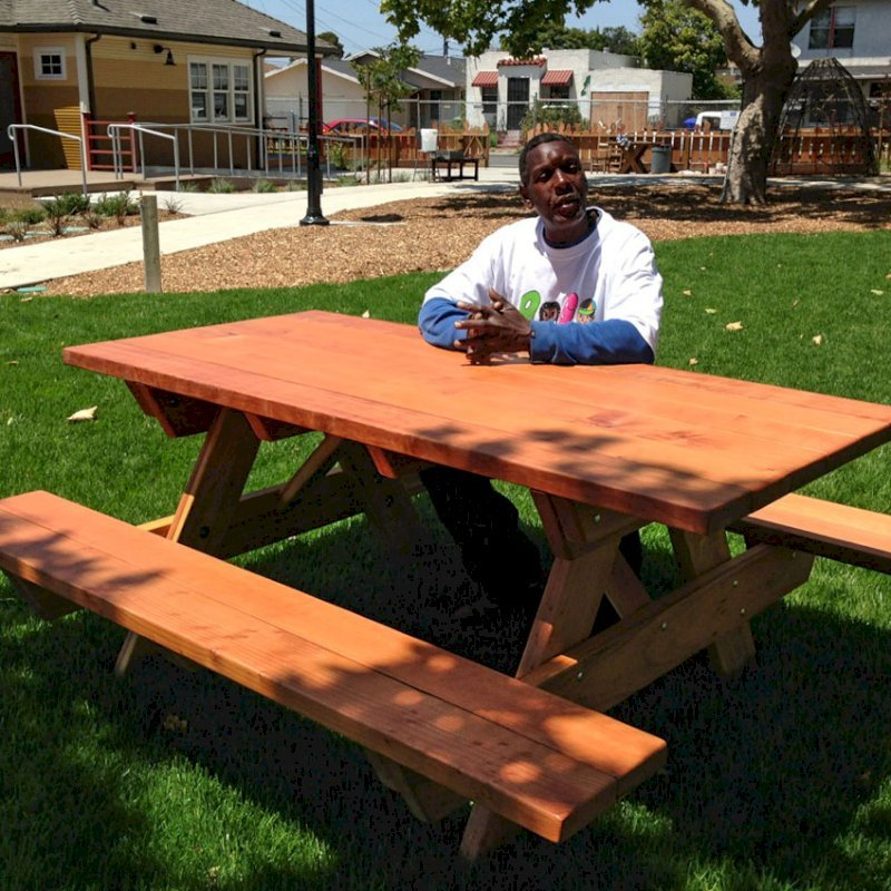 "Forever Picnic Table (Options: 6' L, 34 1/2"" W, Side Benches, California Redwood, Standard Tabletop, SlightlyRounded Corners, No Umbrella Hole, Transparent Premium Sealant). Photo Courtesy of Pogo Park of Richmond, CA (www.pogopark.org)."