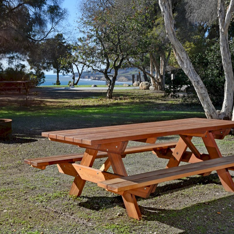 "Forever Picnic Table (Options: 8' L, 34 1/2"" W, Side Benches, California Redwood, Standard Tabletop, Slightly Rounded Corners, No Umbrella Hole, Transparent Premium Sealant). Located at El Capitan State Beach near Santa Barbara, CA part of a 90 table installation completed in 2015."