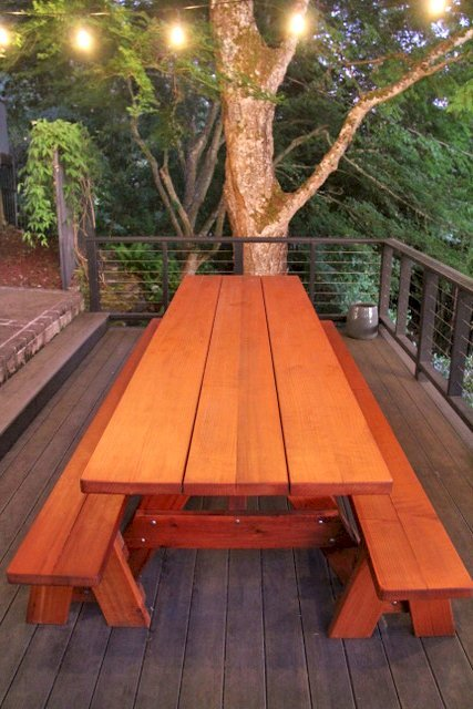 "Custom Forever Picnic Tables (Options: 10' L, 34 ½"" W, Mature Redwood, 1 Full Length Bench Per Side, Standard Tabletop, Slightly Rounded Corners, No Umbrella Hole, Transparent Premium). Using Two Tongue & Groove Matching 5 3/4"" Boards to Create the Appearance of an 11 1/2"" Wide Board Construction. Photo courtesy of E. Johnson of Eugene, Oregon."