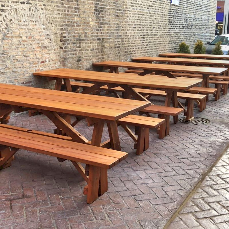 "Foreorever Picnic Tables (Options: 10', 34 1/2"" W, Side Benches, Mature Redwood, 1 Full Length Side Bench Per Side, Standard Tabletop, Squared Corners, 2"" Umbrella Hole, Transparent Premium Sealant). Standard design is with 5 3/4"" wide boards. The tabletops in this photo were built for the restaurant by request using bookend construction (where 2 standard width 5 3/4"" wide boards are tongue and grooved together to appear as one wider 11 1/2"" wide board). If you would like this effect for your tables, just add a note saying want bookend detail added to your order (no extra charge to do this). Photo courtesy of M. Piekarz of Chicago, IL."