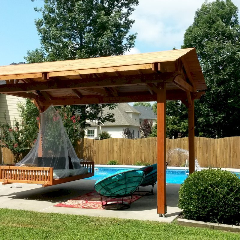 """Jhoola Day Bed Swing (Options: 7' L, 60"""" W, Seat Only, California Redwood, All Beam Hanging Hardware, Add 3 Railings (North, South and extra one, East or West), Day Bed Style, No Cushion, Transparent Premium Sealant). Also shows a Del Norte Pavilion."""