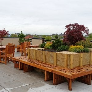 Custom Square Lighthouse Garden Bench (Options: 11 1/2 ft x 14 ft with an Opening in the Center for Planter, 21 1/4 inches W x 18 inches H, Redwood, No Cushion, No Engraving, Transparent Premium Sealant). Photo also shows two Square Patio table sets with Ruth Chairs, and some Mendocino Planters. Photo Courtesy of A. Guttman of Brooklyn, NY.