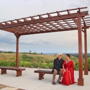 Lighthouse Garden Benches (Options: 4.5 ft L x 17 3/4 inches W x 17 inches H, California Redwood, No Cushion, No Engraving, Coffee-Stain Premium Sealant). Benches Under a Traditional Garden Pergola. Photo Courtesy of Vinod & Aruna.