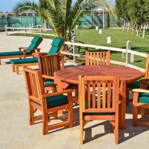 Lisa's Dining Table (Options: 5' Diameter, Chairs, Redwood, with 6 Ruth Armchairs with Forest Green Cushions, Standard Tabletop, No Lazy Susan, No Umbrella Hole, Transparent Premium Sealant). Photo Also Shows 2 Pool Loungers.