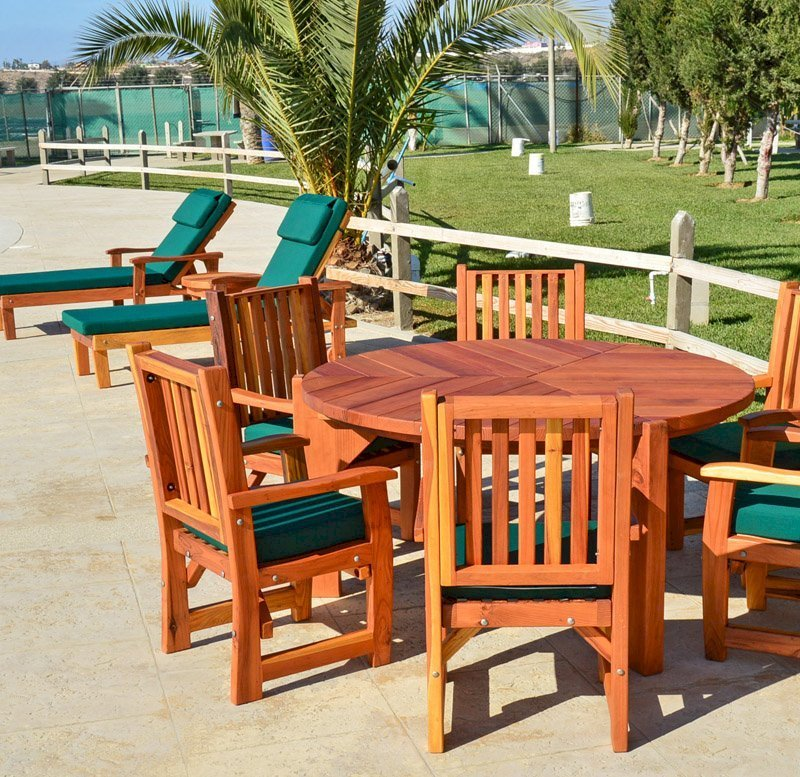 Lisa's Dining Table (Options: 5' Diameter, Chairs, California Redwood, with 6 Ruth Armchairs with Forest Green Cushions, Standard Tabletop, No Lazy Susan, No Umbrella Hole, Transparent Premium Sealant). Photo Also Shows 2 Pool Loungers.