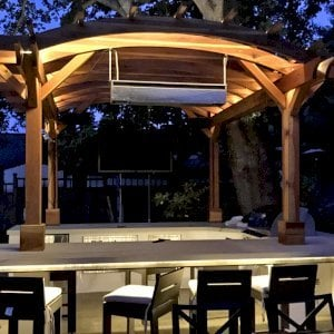 Marin Outdoor Kitchen Pergola (Options: 14' L x 14' Arc W, California Redwood, Unattached, 2 Post Electrical Wiring Trim, 4 Post Anchor Kit for Stone, No Ceiling Fan Base, No Privacy, No Curtain Rods, 9 ft Post Height (front posts wrapped with masonry), Transparent Premium Sealant). Photo Courtesy of C. Funkhouser of Hillsborough, California.