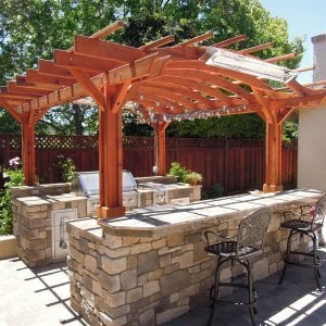 Marin Outdoor Kitchen Pergola (Options: 14' L x 16' Arc W, Redwood, Unattached, 2 Post Electrical Wiring Trim, Arched Roof without Lattice Panels, 4 Post Anchor Kit for Stone, No Ceiling Fan Base, No Privacy, No Curtain Rods, 9 ft Post Height (front posts wrapped with masonry), Transparent Premium Sealant).