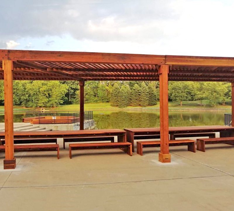 "Maynard Table (Options: 15' L, 42"" W Tabletop, Side Benches, California Redwood, 2 Half Length Maynard Benches Per Side, Standard Tabletop, No Umbrella Hole, Transparent Premium Sealant). Tables Under a Silverado Modern Pergola. Photo Courtesy of A. Arena of Morristown, New Jersey."