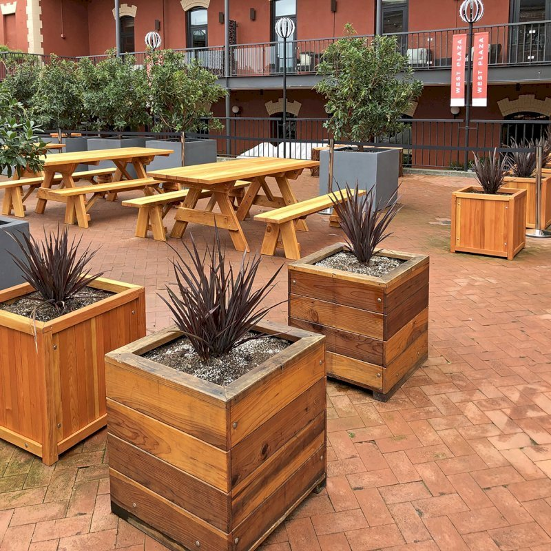 "Mendocino Planters (Options: 24""L, 24""W, 24""H, Redwood, With 1 3/4"" Feet, No Trellis, Interior of Planter With Sealant, Transparent Premium Sealant). Photo also shows some Forever Picnic Tables and some Napa Platers. Horizontal board planters (Mendocino Planters) were initially installed in 2015 and this is why the finish is a bit darker than the Napa Planters. Photo Courtesy of D. Harty of San Francisco, CA."