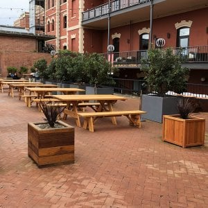 "Napa Planters (Options: 30"" L x 30"" W x 30"" H, Redwood, With 1-inch feet, No Trellis, No Growing Vegetables, Transparent Premium Sealant). Photo also shows some Forever Picnic Tables and some Mendocino Planter. Horizontal board planters (Mendocino Planters) were initially installed in 2015 and this is why the finish is a bit darker."