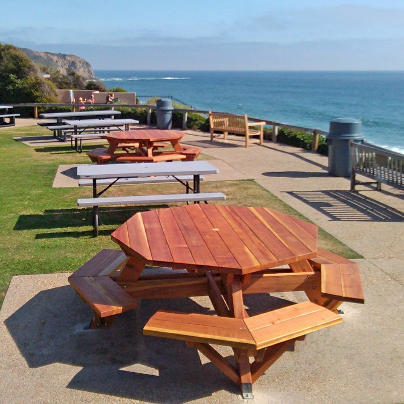 "Octagonal Picnic Tables (Options: 5 1/2' Diameter Tabletop, Attached Benches, Redwood, Standard Tabletop, 1 5/8"" Umbrella Hole, Transparent Premium Sealant). Photo Courtesy of G. Cooley of Dana Point, CA. Plastic gray tables not made by Forever Redwood!"