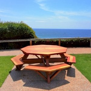 "Octagonal Picnic Table (Options: 5.5' Diameter Tabletop, Attached Benches, Redwood, Standard Tabletop, Rounded Corners, 1 5/8"" Diameter Umbrella Hole, Transparent Premium Sealant). Photo Courtesy of C. Cooley of Dana Point, CA."