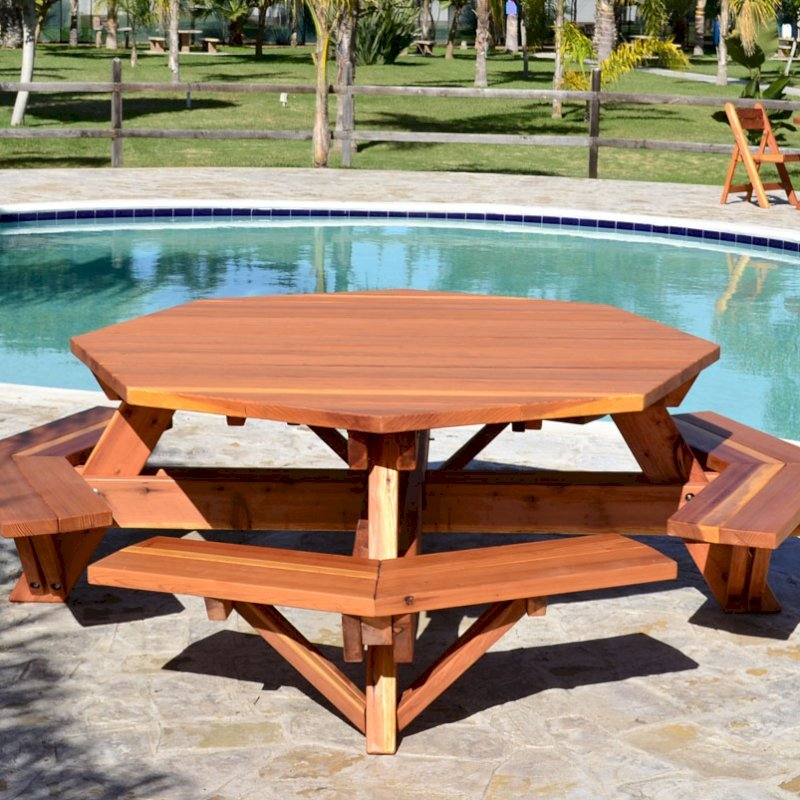 Octagonal Picnic Table (Options: 6' Diameter Tabletop, Attached Benches, Mature Redwood, Standard Tabletop, Rounded Corners, No Umbrella Hole, Transparent Premium Sealant). Round Folding Table with Chairs in Background.