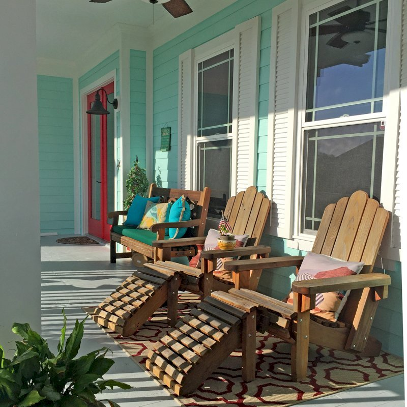 Adirondack Chairs with Ottomans (Options: Standard Size, Redwood, No Cushion, Transparent Premium Sealant). When photographed the finish was 3 years old. Photo also shows a Hennell bench in the background. Photo Courtesy of L. Davies of The Villages, Florida.