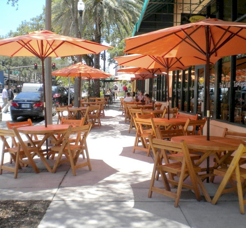 "Redwood Round Folding Table (Options: 42"", 4 Folding Chairs, Douglas-Fir, No Cushions, Standard Tabletop, Checkerboard Design, Visible Screw Placement, Umbrella Hole, Transparent Premium Sealant). Photo Courtesy of Messineo's Gourmet Market, St. Petersburg, FL."