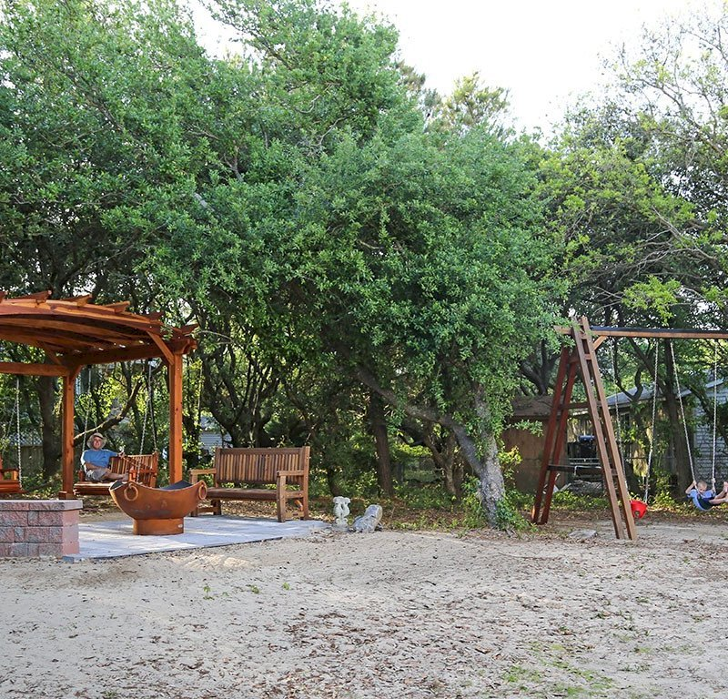 Rory's Giant Playground Swing Set (Options: 3 Seats, Redwood, Standard Swing Seats, Transparent Premium Sealant). Photo Also Shows an Arched Pergola with Swing Benches and a Ti Amo Bench. Photo Courtesy of Tom Marten of Kitty Hawk, NC.
