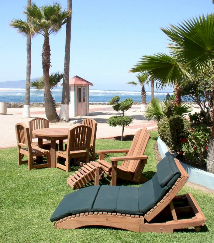 """Penny's Lounger, Round Patio Table with Luna Chairs & Adirondack Chair set. Note: the 7 section, 2"""" thick cushion shown was a custom order. Photo Courtesy of Estero Beach Resort of Ensenada, Baja California Mexico."""