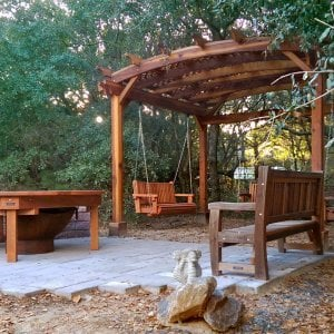 Round Patio Table (Options: 6.5 ft, No Seating, Redwood, Standard Tabletop, No Lazy Susan, No Umbrella Hole, Transparent Premium Sealant, Braces Underneath Tabletop by Custom Request). Photo Also Shows an Arched Pergola with 3 Bench Swings and a Ti Amo Bench. Photo Courtesy of Tom Marten of Kitty Hawk, NC.