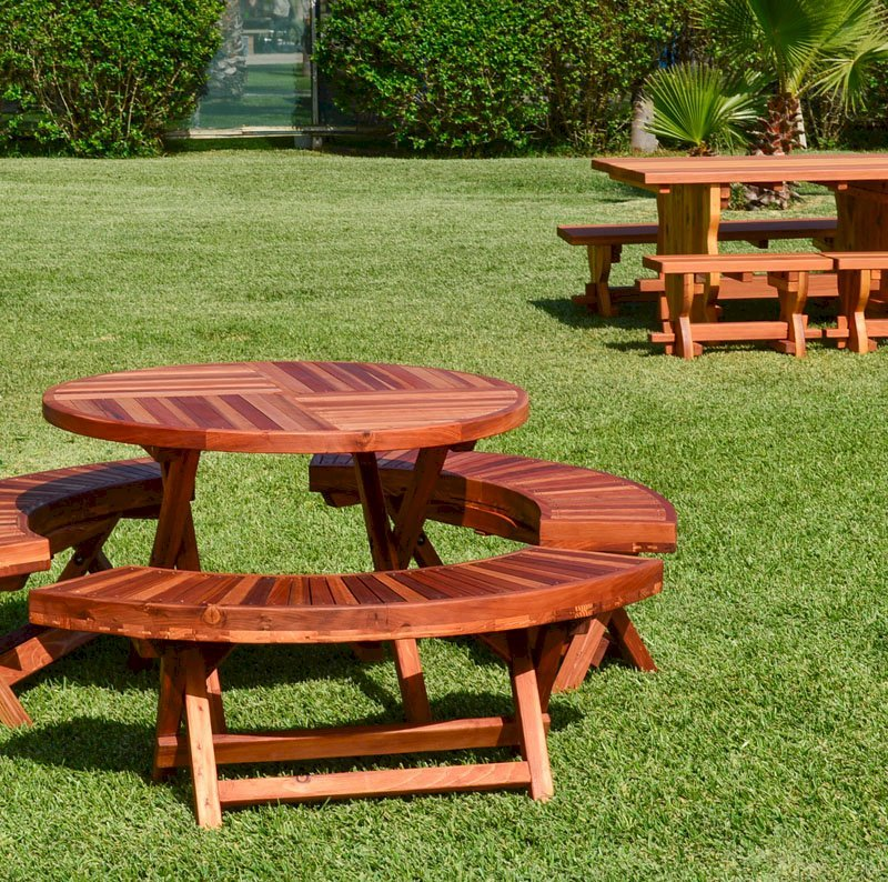 "Round Folding Picnic Table (Options: 42"", Folding Arc Benches, Redwood [with some Mosaic Eco-Wood boards at the bottom of the seat by custom request], 3 Folding Arc Benches, Standard Tabletop, Checkerboard Design Tabletop, Umbrella Hole & Plug, Transparent Premium Sealant). Photo shows a Trestle Table in Background."