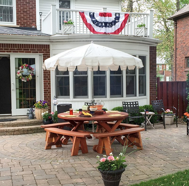 """Round Picnic Table with Wheels (Options: 5.5' Diameter, Unattached Benches, Mature Redwood, Round Picnic Benches, Standard Tabletop, 20"""" Lazy Susan, Umbrella Hole & Plug, Transparent Premium Sealant). Photo Courtesy of Dorothy and Sam Cusmano of Grosse Pointe Park, Michigan."""