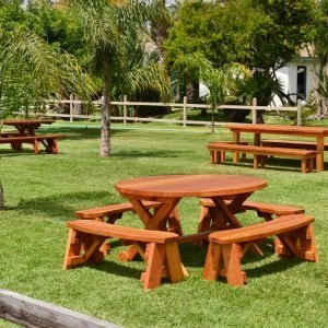 Round Picnic Table with Wheels (Options: 5' Diameter, Unattached Benches,  Redwood, Round Picnic Benches, Standard Tabletop, No Lazy Susan, No Umbrella Hole, Transparent Premium Sealant). Rectangular Picnic Table and Rectangular Patio Table in background.