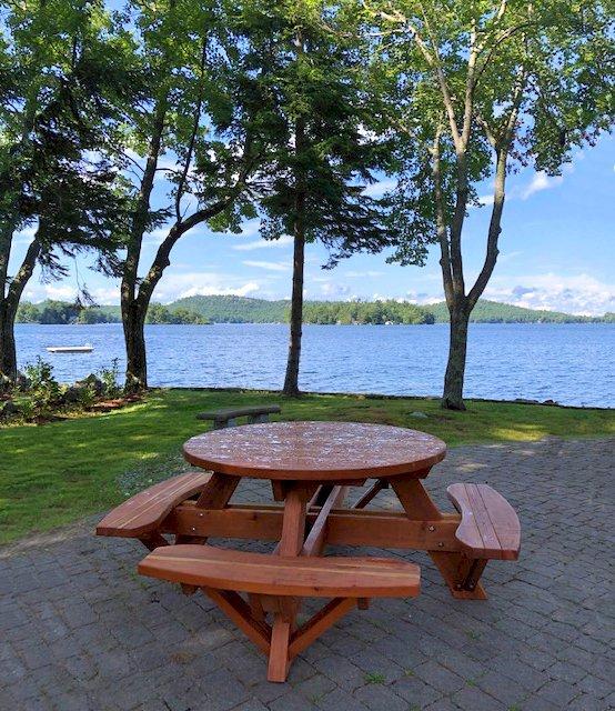 Round Picnic Table (Options: 4.5' Diameter, Attached Benches, Redwood, Standard Tabletop, No Lazy Susan, No Umbrella Hole, Transparent Premium Sealant). Photo Courtesy of Debbie Awalt of Alton Bay, New Hampshire.