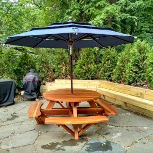 Round Picnic Table (Options: 5' Diameter, Attached Benches, Redwood, Standard Tabletop, No Lazy Susan, 1 5/8 Umbrella Hole & Plug, Transparent Premium Sealant). Photo Courtesy of S. Shilagani of Great Neck, New York.