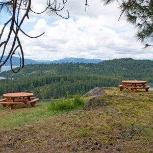 "Round Picnic Tables (Options: 6' Diameter, Attached Benches, Redwood, Standard Tabletop, No Lazy Susan, Umbrella Hole & Plug, Transparent Premium Sealant). These beautiful tables are installed at the ""Bull Pine Ledge"", looking out on Lake Pend Orielle from Cloudsledge Conservation Trust, Hope Idaho. Photo Courtesy of Art Green."