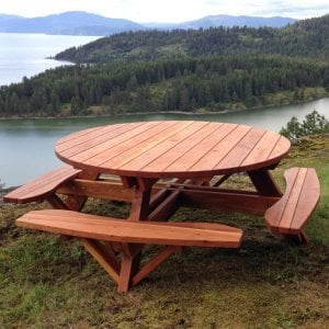 "Round Picnic Table (Options: 6' Diameter, Attached Benches, Redwood, Standard Tabletop, No Lazy Susan, Umbrella Hole & Plug, Transparent Premium Sealant). These beautiful tables are installed at the ""Bull Pine Ledge"", looking out on Lake Pend Orielle from Cloudsledge Conservation Trust, Hope Idaho. Photo Courtesy of Art Green."