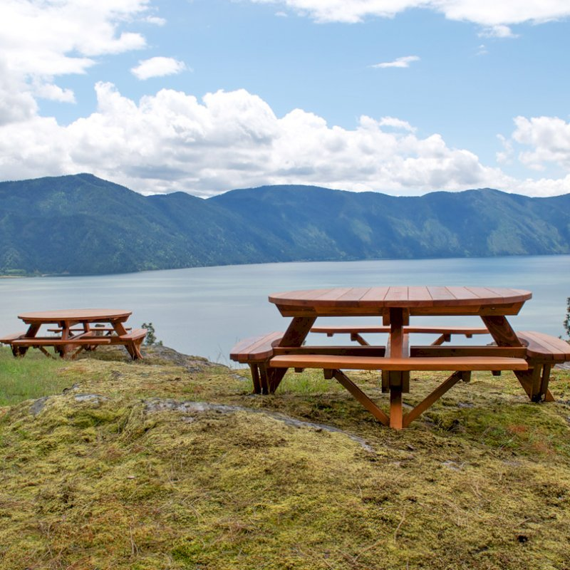 """Round Picnic Tables (Options: 6' Diameter, Attached Benches, Redwood, Standard Tabletop, No Lazy Susan, Umbrella Hole & Plug, Transparent Premium Sealant). These beautiful tables are installed at the """"Bull Pine Ledge"""", looking out on Lake Pend Orielle from Cloudsledge Conservation Trust, Hope Idaho. Photo Courtesy of Art Green."""