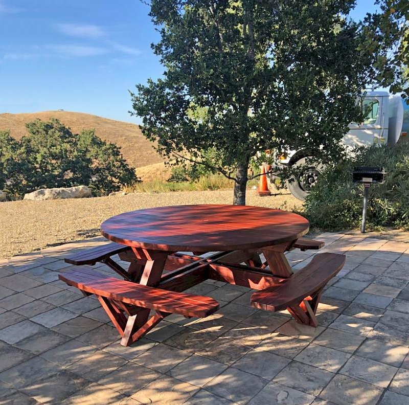 """Round Picnic Table (Options: 6' Diameter, Attached Benches, Mature Redwood, Standard Tabletop, No Lazy Susan, 1 5/8"""" Diameter Umbrella Hole, Transparent Premium Sealant). Photo Courtesy of W. Fry of Lafayette, California."""