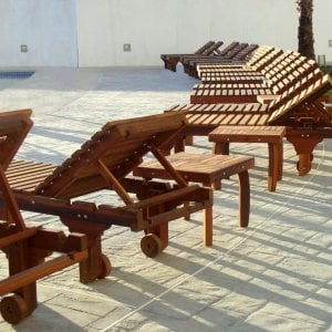 "Sol Loungers (Options: Single, Standard 74"", Mature Redwood, 13"" H, Wheels, No Cushion, Transparent Premium Sealant). Terrace Side tables shown between some of the Loungers."