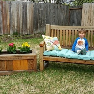 "Sonoma Planter (Options: 48"" L, 18"" W x 18"" H, Redwood, No Seating Ledge, 1"" Feet, No Trellis, Custom Engraving, No Growing Vegetables, Transparent Premium Sealant). Photo Also Shows a Ti Amo Bench. Photo Courtesy of Rebecca Rasmussen of Anchorage, Alaska. Faded finish is because photo taken 4 years after it was built."