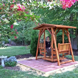 St. Anthony's Face to Face Glider (Adult Size, Redwood, No Beverage Armrests, No Kid's Platform, Standard Closed Roof, No Engraving, Transparent Premium Sealant). Photo Courtesy of Dulce B. of Yorktown, VA.