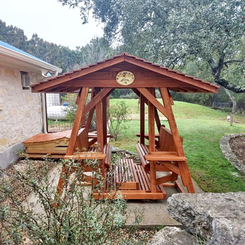 St. Anthony's Face to Face Glider (Options: Extra Wide Size, Mature Redwood, With Beverage Armrests, No Kid's Platform,  XW Roof, No Engraving, Transparent Premium Sealant). Photo Courtesy of R. Vincent of Wimberly, Texas.