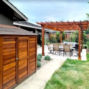 """Storage Shed (Options: 7' W, 4.5' D, 7' H, Redwood, Single Door, One Shelf on the Side Opposite the Door, 42"""" H, Transparent Premium Sealant). Photo Also Shows a Garden Pergola in the Background. Photo Courtesy of J. Lewis of Mountain View, CA."""