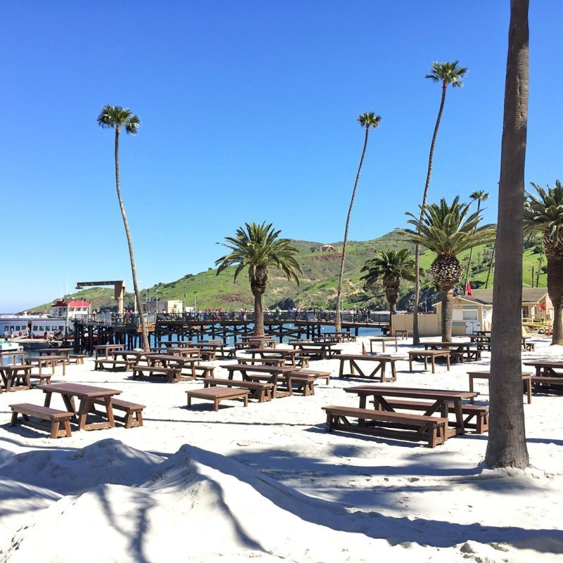 The Classic Redwood Patio Table (Options: California Redwood, Side Benches, 1 Full Length Bench Per Side, Standard Tabletop, Slightly Rounded Corners, No Umbrella Hole, Coffee Stain Premium Sealant). Photo Shows Customized Version of Patio Tables. Tables Installed in Catalina Island, CA.
