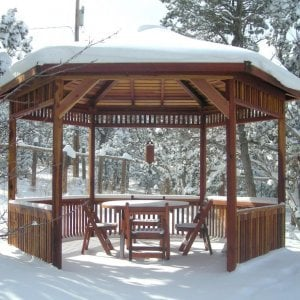 The Hexagonal Retreat Pavilion (Options: 14' Diameter, No Deck, Redwood, With Upper and Lower Panels, Transparent Premium Sealant).  Round Folding Table Set with Chairs Under Pavilion. Photo Courtesy of Ms. Karen McCartney of Tijeras, NM.