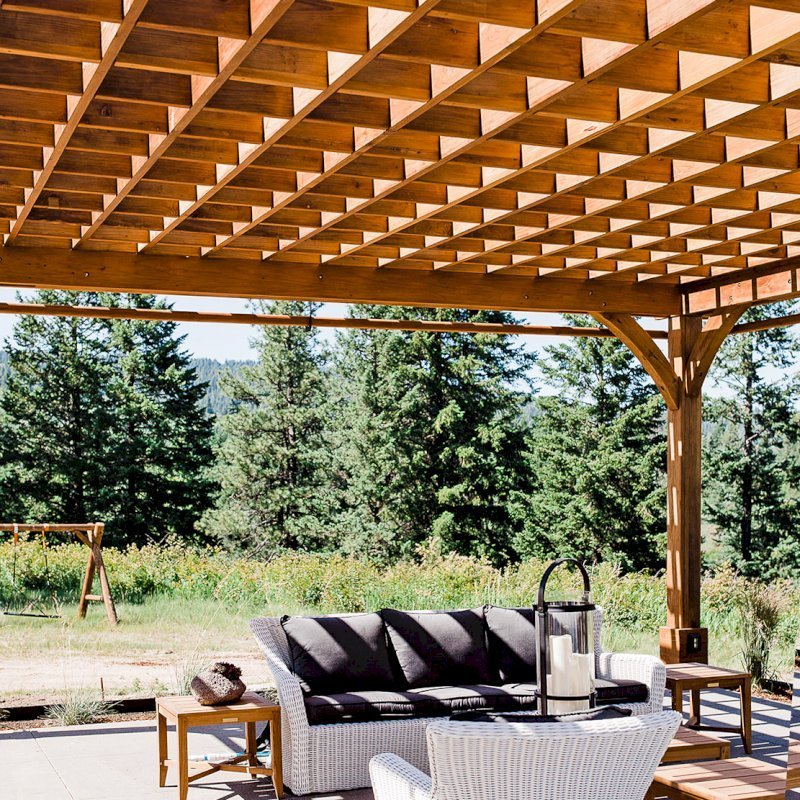 The Montvale Pergola  (Options: 22' x 22', Mature Redwood, Post Anchoring for Concrete, Electrical Wiring Trim Kit for 4 Posts, No Ceiling Fan Base, 4 Curtain Rods, No Privacy Panels, 10' Post, Transparent Premium Sealant). Photo Courtesy of J. Scott of Coeur deline, Idaho.
