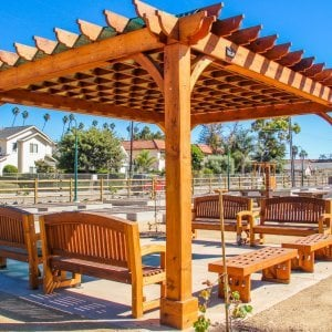 The Montvale Pergola (Options: 16' x 20', Mature Redwood, Post Anchoring for Concrete, No Ceiling Fan Base, No Curtain Rods, No Privacy Panels, 9.5' Post, Transparent Premium Sealant). Photo also shows some Luna Memorial Benches and Lighthouse Benches. Sunbrella shade fabric above the pergola was ordered from: www.patiolane.com as a custom item. Photo Courtesy of Carpinteria Park, 5775 Carpinteria Avenue  Carpinteria, CA  93013.