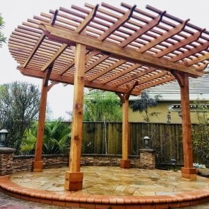 "The Round Pergola (Options: 16' Diameter, No Privacy Panel, Redwood, Open Roof Slats at 6"", 9.5ft Post height, Include Electrical Wiring Trim for 2 Posts, 4-Post Anchor Kit for Stone or Concrete, No Post Decorative Trim, No Ceiling Fan Base, No Curtain Rods, Transparent Premium Sealant). Photo courtesy of Harish B. of Dublin, CA"
