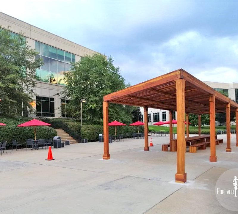 """The Silverado Modern Pergola (options: 58' L, 16' W, Redwood, No Electrical Wiring Trim, with 1 3/4"""" x 11 1/4"""" Roof Support Timbers and 7 1/4"""" x 7 1/4"""" Posts, 8 Post Anchor Kit for Concrete, No Privacy Panels, No Curtain Rods, 10' Post Height, Transparent Premium Sealant). Photo Also Shows 2 Maynard Modern Redwood Patio Table Sets Under the Pergola. Photo Courtesy of A. Arena of Morristown, New Jersey."""